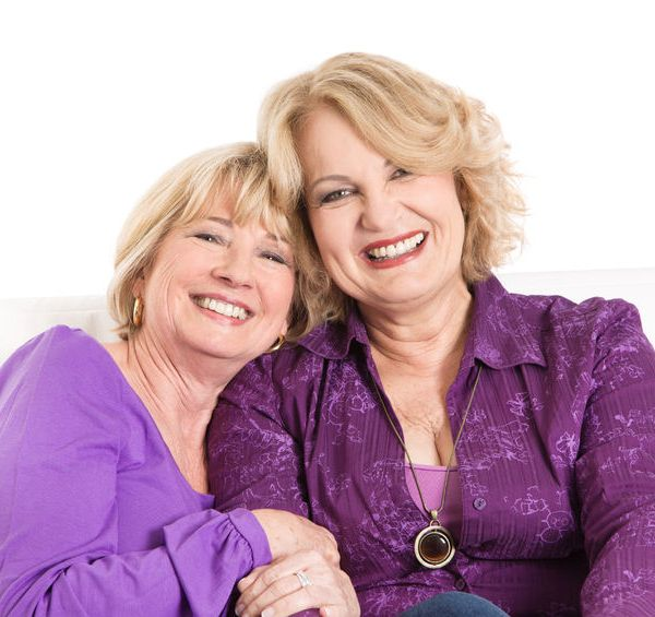 24686241 - portrait of two older women smiling in purple or violet shirts